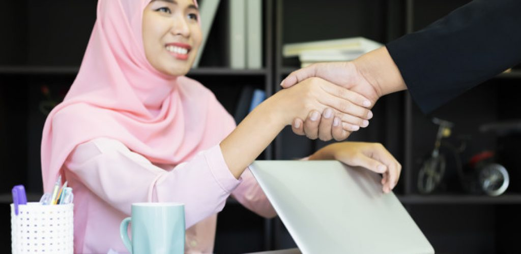 Muslim islam Business Handshaking. Asian woman muslim shirt pink. Business women hand with paper writing at graph, Using Computer Notebook laptop and smartphone, Felling happy Marketing business for success Concept.