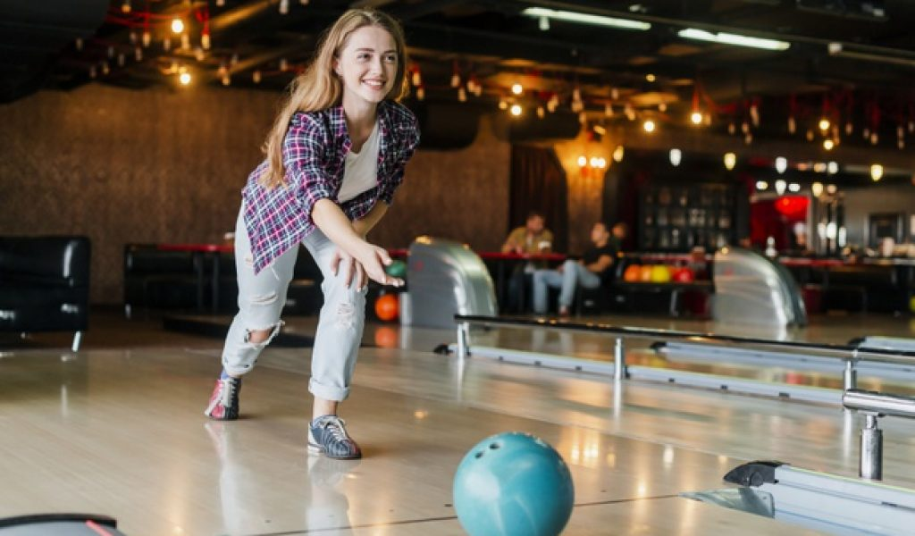 young-woman-playing-with-bowling-ball_23-2148344403